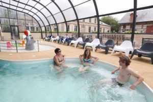 Détente au bord de la piscine couverte chauffée au camping La Baie de Somme au Crotoy